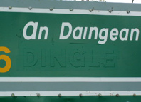 Irish Road sign close up showing outline of the name Dingle under the green tape